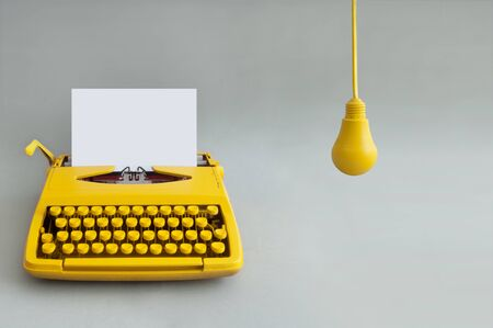 Retro typewriter with yellow hanging light bulb, representing inspiration and new ideas 版權商用圖片 - 133010675