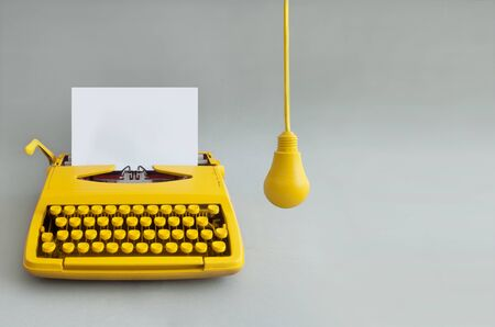 Retro typewriter with yellow hanging light bulb, representing inspiration and new ideas
