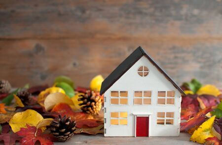 Miniature house surrounded by autumn leaves