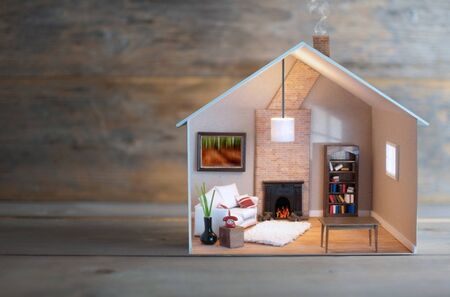 Model house with lights on inside over wood with space Stockfoto