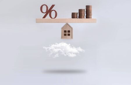 Percentage sign and stack of coins seasaw balanced on a miniature house hovering above the clouds, mortgage, investment concept
