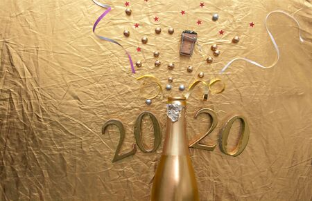 Gold champagne background, confetti and baubles coming out of a bottle with 2020 letters