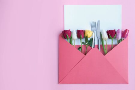 Envelope with assorted roses and tulips and knife and fork in the centre with blank sheet of paper