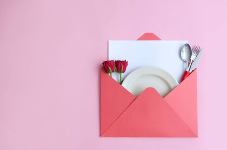 Valentines day meal, plate with cutlery and two red roses inside an envelope Reklamní fotografie