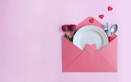Valentines day roses, plate and cutlery inside an envelope Reklamní fotografie