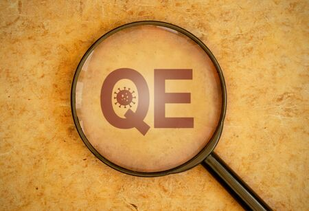 Magnifying glass focusing on QE for quantitative easing with coronavirus symbol  Фото со стока