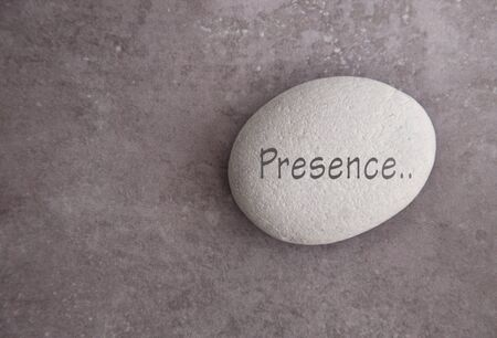 Yoga zen stone with the word presence Standard-Bild