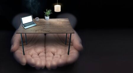 Hands outstretched holding a miniature office desk with laptop and lamp and hot coffee