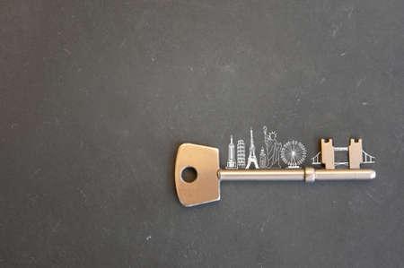 Gold key with skyline sketch of global landmarks