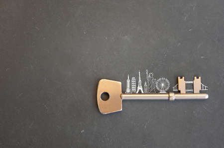Gold key with skyline sketch of global landmarks