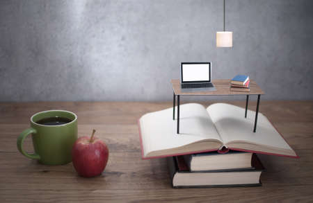 Miniature desk with laptop on top of open books