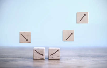 Business recovery concept; building blocks mid air with arrows first heading down then in an upwards direction