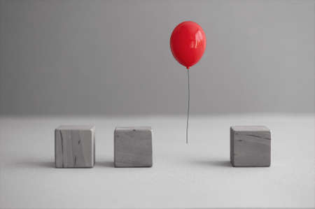 Red balloon mid air amongst wooden square cubes