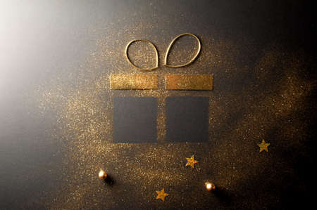 Gift box shape made with gold glitter and ribbon bow Standard-Bild