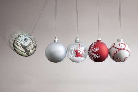 Dollar bauble colliding into christmas ornaments, seasonal shopping budget and balancing finances concept Standard-Bild