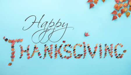 Thanskgiving greeting created with autumnal leaves, pumpkin and pine cones