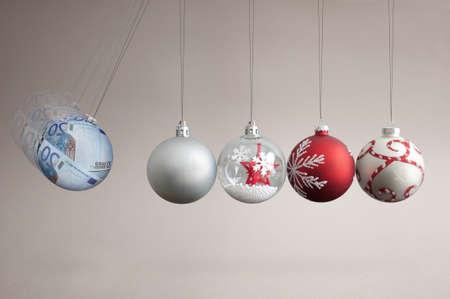 Euros bauble colliding into christmas ornaments, seasonal shopping budget and balancing finances concept Standard-Bild