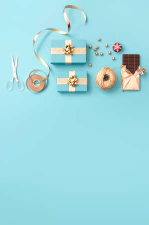 Top view of gift boxes wrapped in gold, baubles, chocolate bar and wrapping accessories