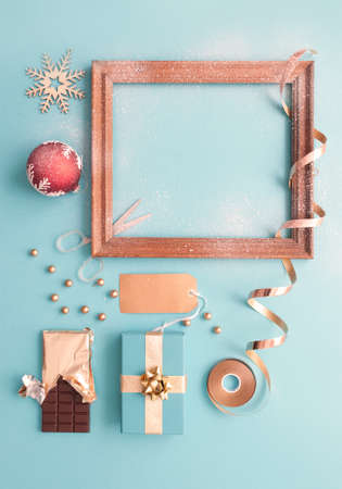 Decorative christmas blank picture frame covered in snow with gifts and wrapping accessories