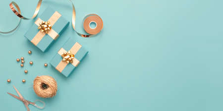 Top view of gift boxes wrapped in gold with baubles, and wrapping accessories