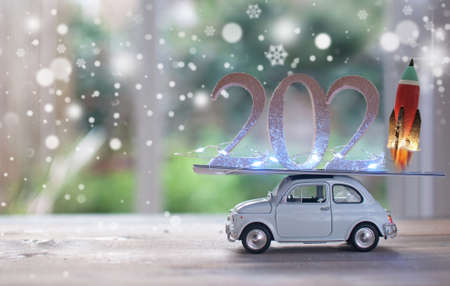 2021 new year eve wooden blocks with light on top of a toy car with rocket in launch mode