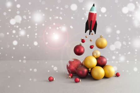 Toy rocket launching with red and gold christmas baubles representing fire and smoke Standard-Bild