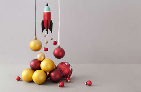 Toy rocket taking off with red and gold christmas baubles representing launch fire Standard-Bild
