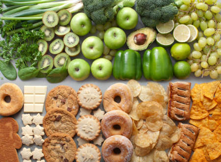 Assorted group of green fruits and vegetables alongside unhealthy christmas food and snacks Standard-Bild