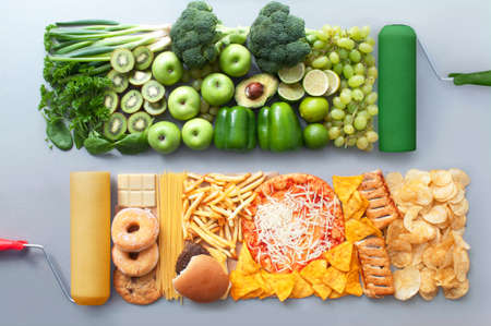 Assorted group of green fruits and vegetables alongside beige junk food with roller brush Standard-Bild