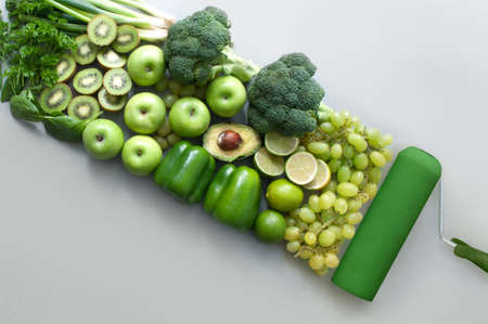 Many green fruits and vegetables following a roller brush stroke, food colour group concept Standard-Bild