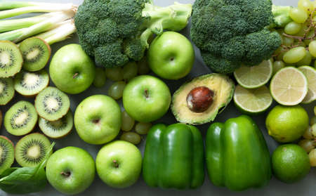 Healthy organic green fruits and vegetables closeup incluing broccoli, apples, kiwi, lime, peppers, and avocado