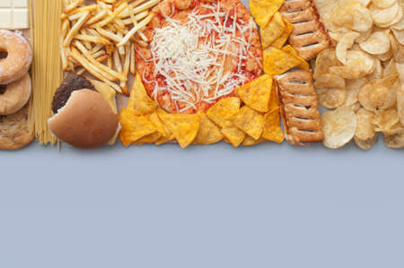 Collection of fast food includnig french fries, pizza, burger and tortilla chips Standard-Bild