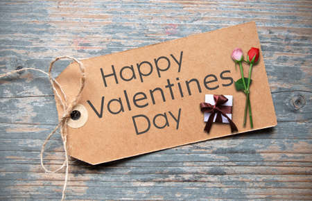 Happy valentines day handwritten on a label with two roses and wrapped gift box Standard-Bild