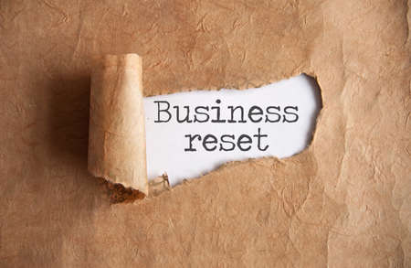 Torn piece of scroll revealing business reset Standard-Bild