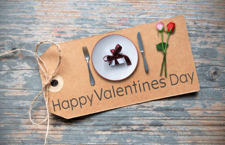 Happy valentines day greeting label with dinner plate, gift box and flowers