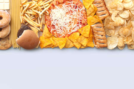 Collection of fast food includnig french fries, pizza, burger and tortilla chips with copy space