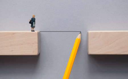 Pencil sketch bridging the gap between wooden blocks for female miniature figure to cross Standard-Bild