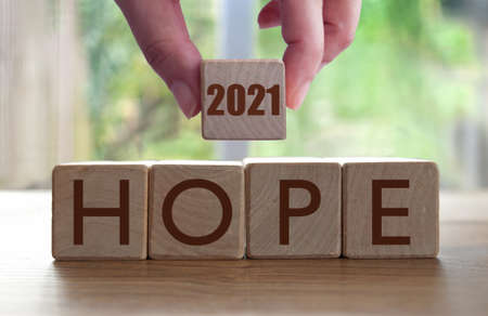 Hope wooden blocks with hand holding 2021