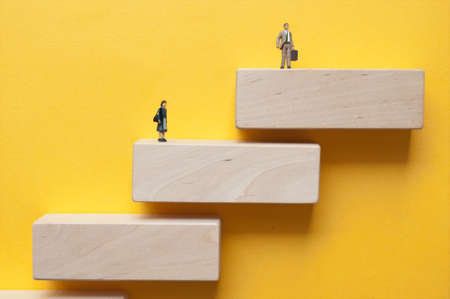 Miniature woman and man standing on wooden steps on different levels Standard-Bild