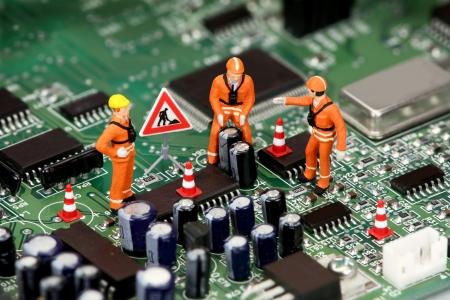 repairing: Miniatura t�cnicos trabajando en una placa de circuito de equipo o de la motherboard. Concepto de apoyo de tecnolog�a.