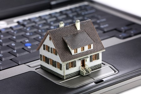 Miniature model home sitting on a laptop keyboard. Real estate on the internet concept. photo