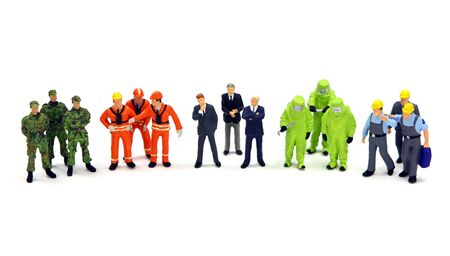 miniature people: A diverse group of workers standing in a row against a white background. Diversity or teamwork concept.