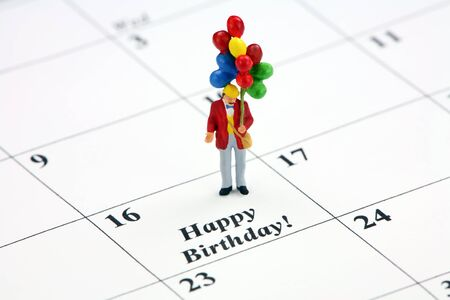 Birthday concept. A miniature man holding a bunch of balloons is standing on a calendar date that says Happy Birthday. Stock Photo