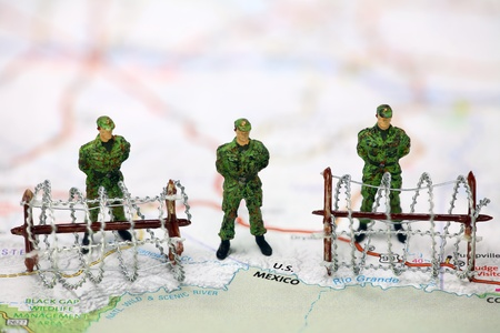 barbed wire and fence: Miniature border patrol guards standing on a map at the USAMexico border with barbed wire. Border protection and immigration concept. Stock Photo