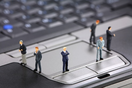 Group of miniature businessmen standing on a laptop. Modern business concept. photo