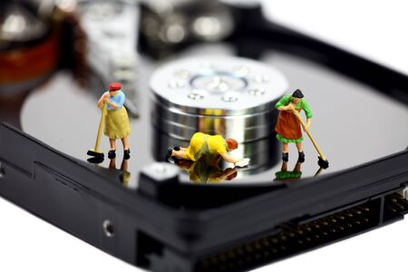 Miniature maids or cleaning women on an open computer hard drive. They are cleaning viruses, spyware and trojans. Computer security concept.