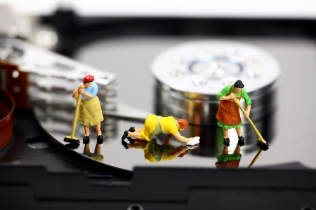 miniature people: Miniature maids or cleaning women on an open computer hard drive. They are cleaning viruses, spyware and trojans. Computer security concept.
