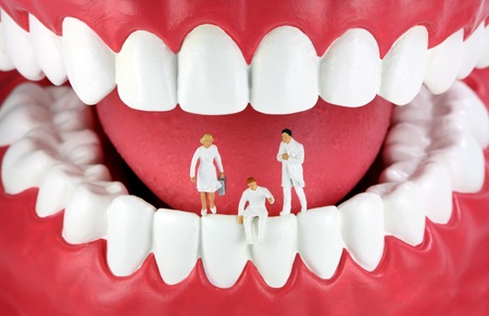 A group of miniature dentists and a dental assistant standingsitting on human teeth.