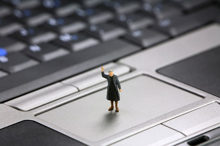 Miniature elderly woman waves for help with her laptop computer. Tech support concept. photo