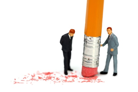 Miniature businessman holds a pencil and erases a mistake while his associate watches. Business mistake concept. photo